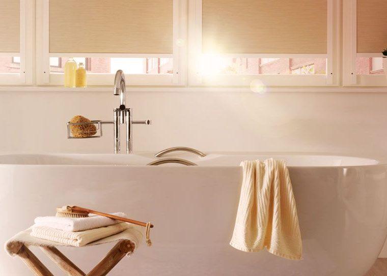 Badewanne vor einem Fenster mit beigen Rollos