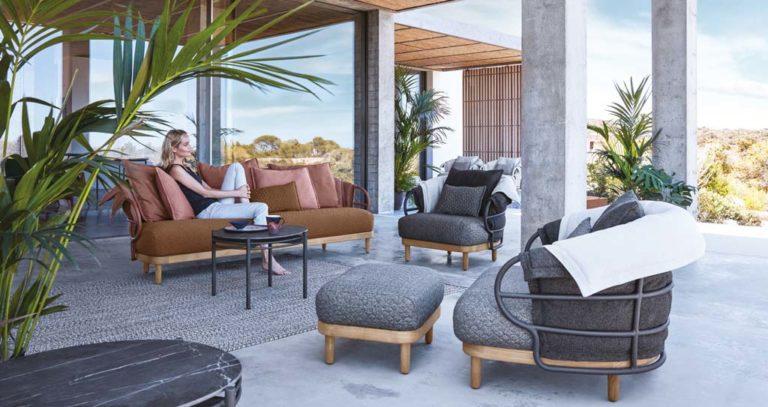 Junge Frau ruht sich auf einer Outdoor-Couch aus