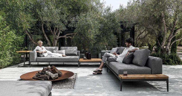 Ehepaar entspannt auf Loungemöbeln mit Feuerschale