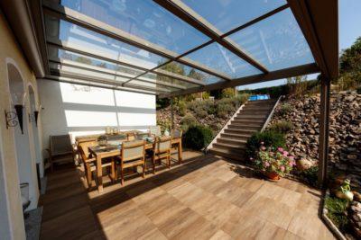Verglastes Terrassendach über Terrasse mit braunem Holzboden