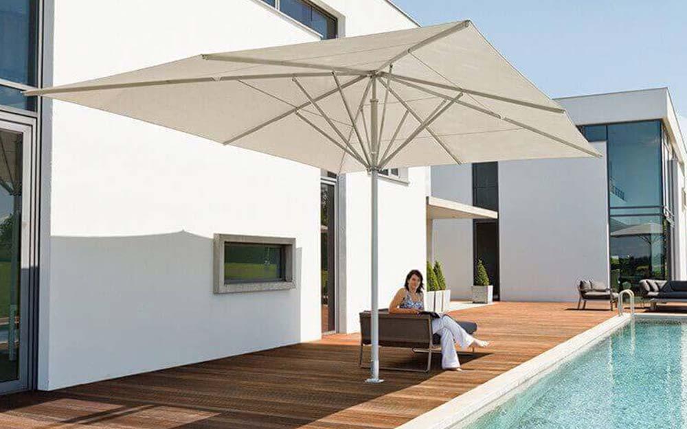 Frau sitzt unter May-Sonnenschirm an Swimmingpool