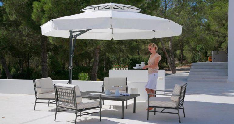 Frau steht unter May-Sonnenschirm mit Tisch und Stühlen