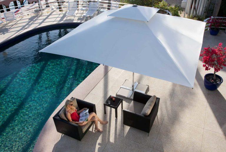 "Frau sitzt unter dem Sonnenschirm-Modell ""Supremo"" an Swimmingpool."