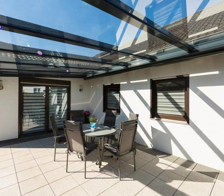 Verglastes Terrassendach neben heller Hausfassade